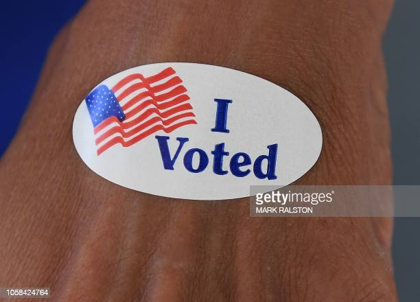 A woman shows an 'I Voted' sticker at an Orange County polling station during the midterm elections in Huntington Beach California on November 6 2018...