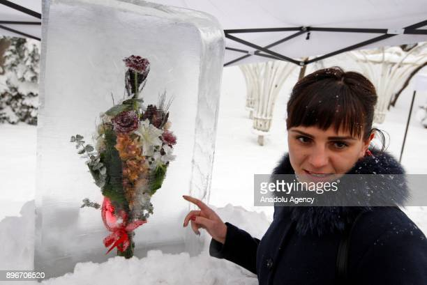 A woman shows an icecovered flower bouquet during the New Year's festival 'Ice Age' on the Pevcheskoye Field in Kiev Ukraine on December 21 2017 The...