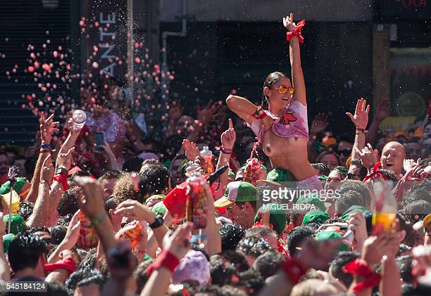 A woman shows her breasts as she celebrates the 'Chupinazo' to mark the kickoff at noon sharp of the San Fermin Festival in front of the Town Hall of...