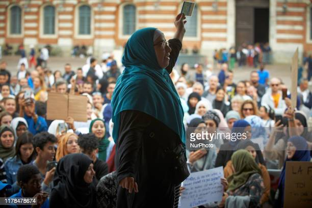 Woman shows her French ID during a rally against islamophobia. People gathered against islamophobia on the main square of Toulouse, the Capitole....