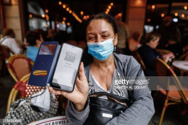 Woman shows her health pass at a coffee shop in Deauville on July 27, 2021. - France's highest constitutional authority said on July 26, 2021 it...