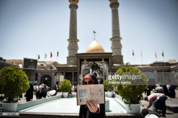 A woman shows her identity as she waits to cast his ballot during Iran's 12th presidential election at Shah Abdol Azim mosque in Tehran Iran on May...