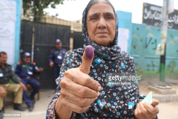 A woman shows her thumb finger with purple ink after casting her vote during Pakistan's general election at a polling station in Karachi on July 25...