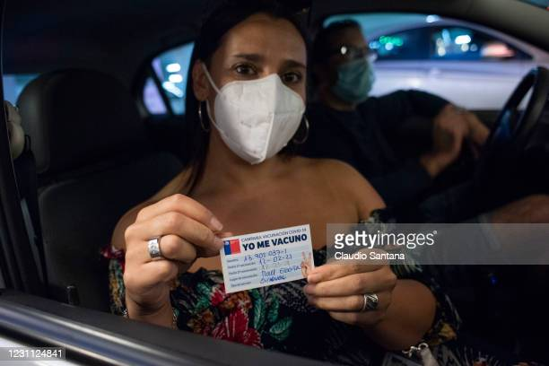Woman shows her vaccination card against COVID-19 at an underground parking lot in the commercial center of the La Reina commune, on February 12,...