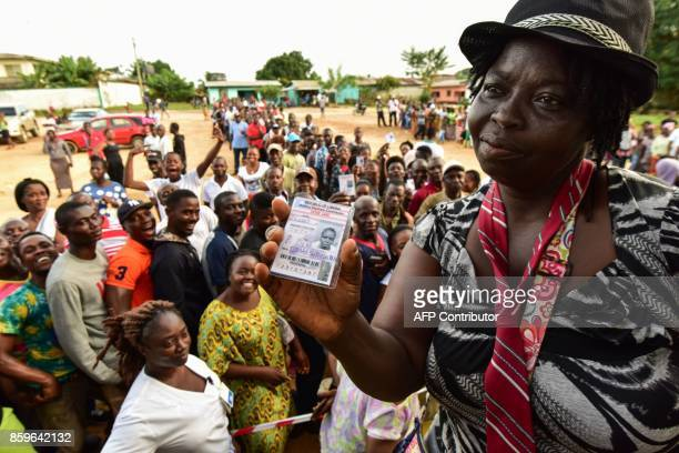 TOPSHOT A woman shows her voting card as people wait in line prior to casting their vote for Liberia's presidential and legislatives elections at a...