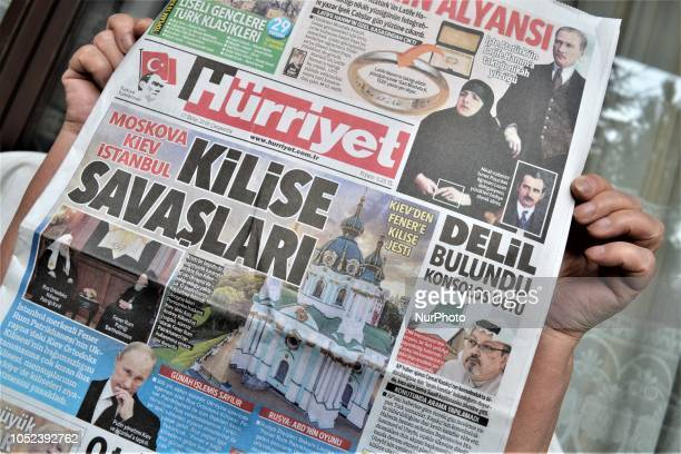 A woman shows Hurriyet a Turkish major daily newspaper as the daily depicts the recent ongoing Orthodox Church crisis between Ukraine and Russia with...