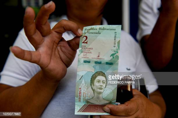 Woman shows new two Bolivar-notes in Caracas on August 20, 2018. - Caracas is issuing new banknotes after lopping five zeroes off the crippled...