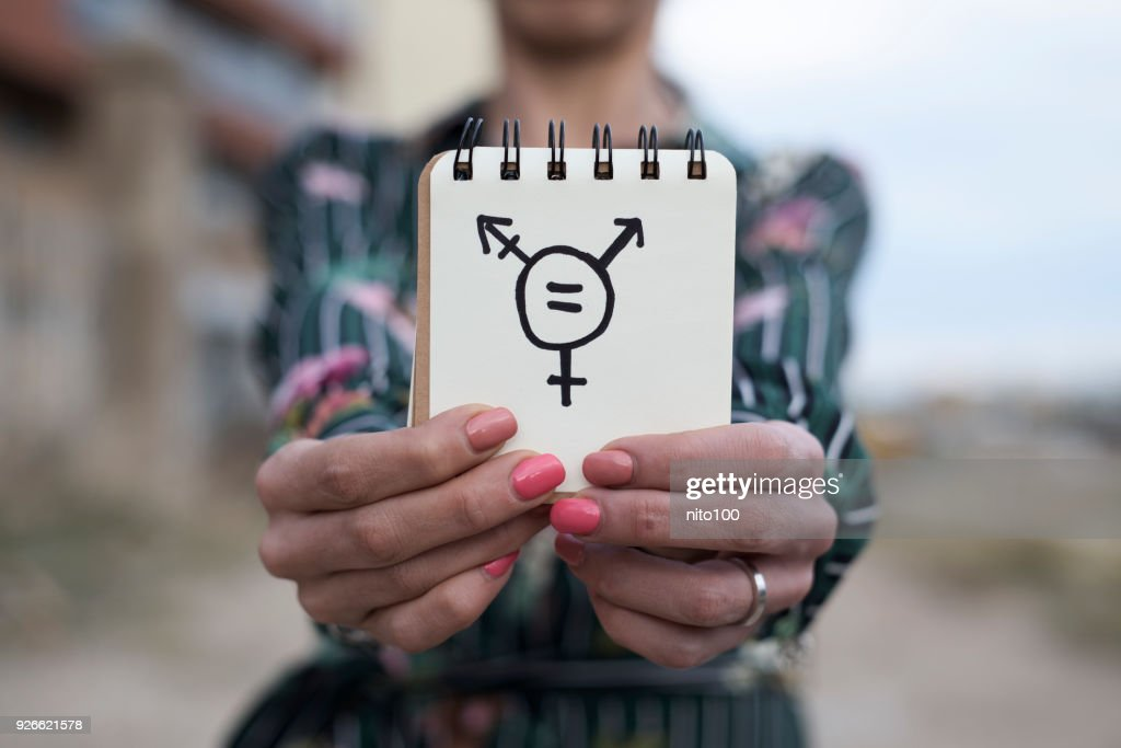 woman shows notepad with a transgender symbol : Stock Photo