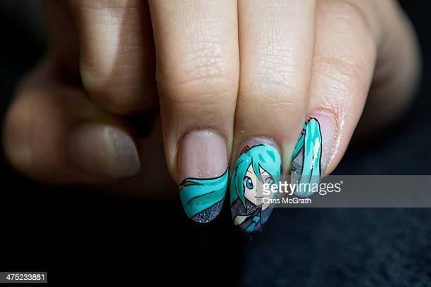 A woman show's off her finished nail art at Ita Color's Yellow nail salon on February 27 2014 in Akihabara district Tokyo Japan Clients are able to...