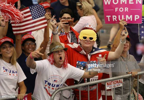 A woman shows off her middle fingers as she and others look on at the media during a campaign rally by President Donald Trump at the AeroMod...