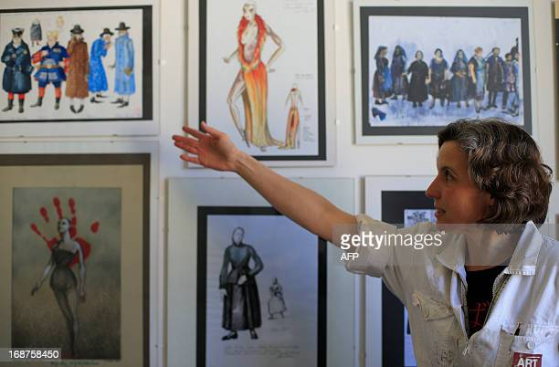 """Woman shows paintings of different costumes at the """"Art for Art"""" costume workshop, producing costumes notably for the Vienna State Opera and various..."""