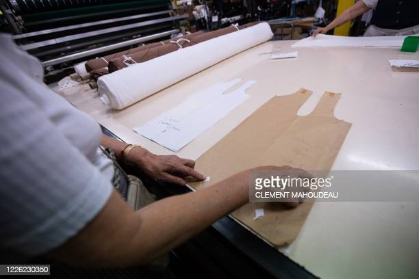 A woman shows patterns used for tank tops in the Sugar clothes brand factory in Marseille south of France on July 10 2020 The brand works with a...
