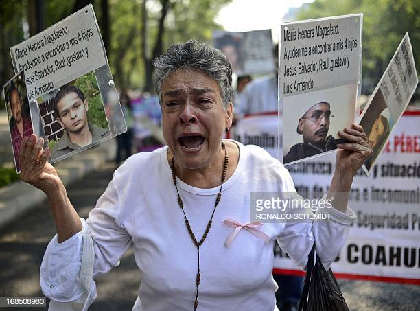 A woman shows pictures of her four sons missing due to the drug war in the country during a protest in Mexico City on May 10 2013 A group of mothers...