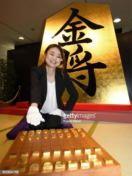 A woman shows pieces made of pure gold for shogi or Japanese chess in front of a giant piece covered in leaf gold at the Takashimaya department store...