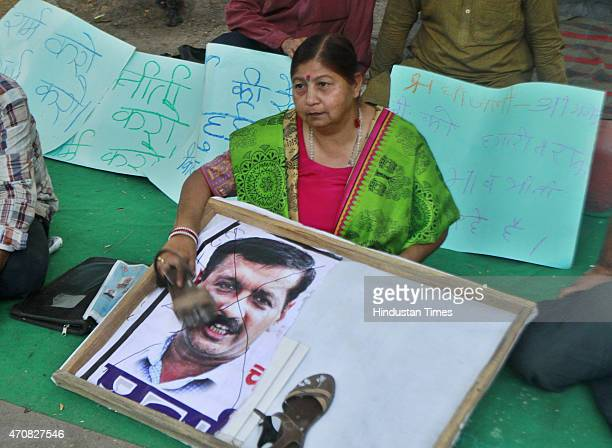 A woman shows sandal to poster of Delhi Chief Minister Arvind Kejriwal during protest at Jantar Mantar over the death of farmer Gajendra Singh who...