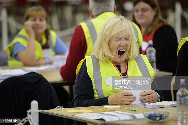 A woman shows signs of fatigue as she counts ballot cards at the Royal Highland Centre counting hall in Edinburgh Scotland on September 19 after...