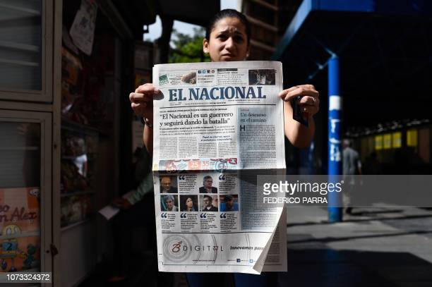 A woman shows the last printed edition of Venezuelan newspaper El Nacional with its front page reading El Nacional is a worrior and will keep on...