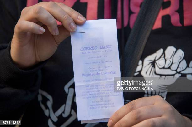 A woman shows the proof of being registered as a marijuana's buyer in Montevideo on May 2 2017 Uruguay which in July will become the first country...