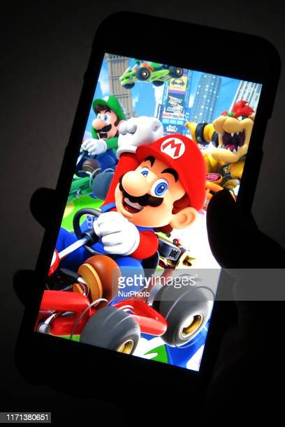 A woman shows the title Mario Kart Tour on her smartphone during game center in Tokyo Japan September 26 2019 After over a year of waiting Mario Kart...