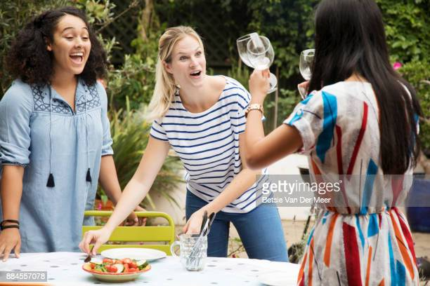 Woman shows the wineglasses to friends setting table for dinner party.