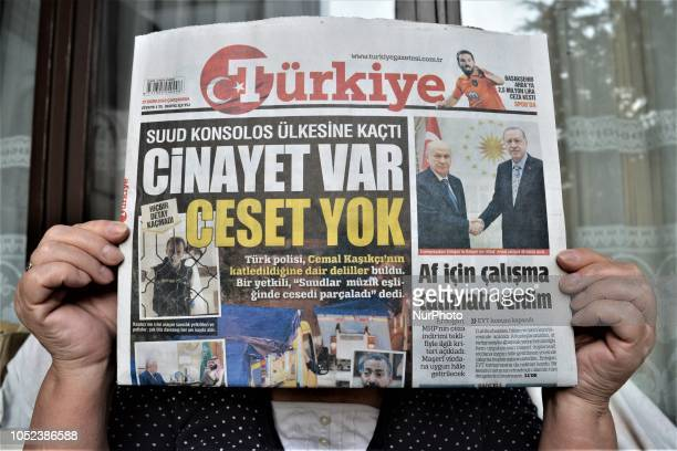 A woman shows Turkiye a Turkish progovernment daily newspaper as the daily runs a headline on its front page that reads 'There is a murder but no...