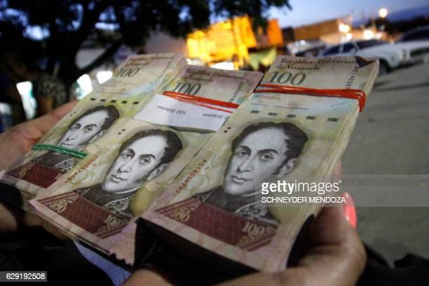 Woman shows wads of 100-bolivar-bills to change in La Parada, municipality of Villa del Rosario, Norte de Santander department, Colombia, in the...