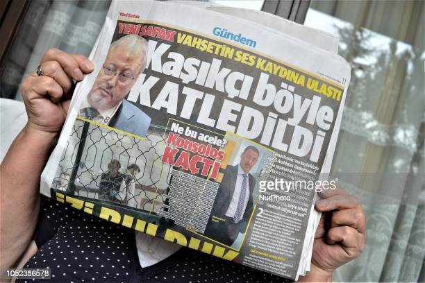 A woman shows Yeni Safak a Turkish progovernment daily newspaper as the daily runs a headline that reads 'This is how Khashoggi was slaughtered' with...
