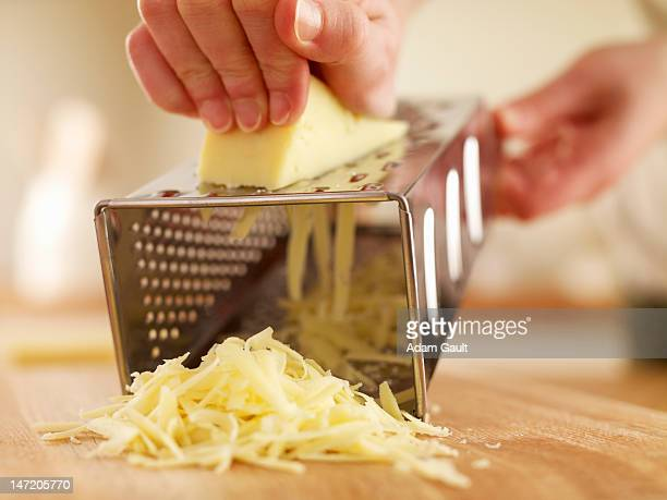 woman shredded cheese with grater - cheese stock photos and pictures
