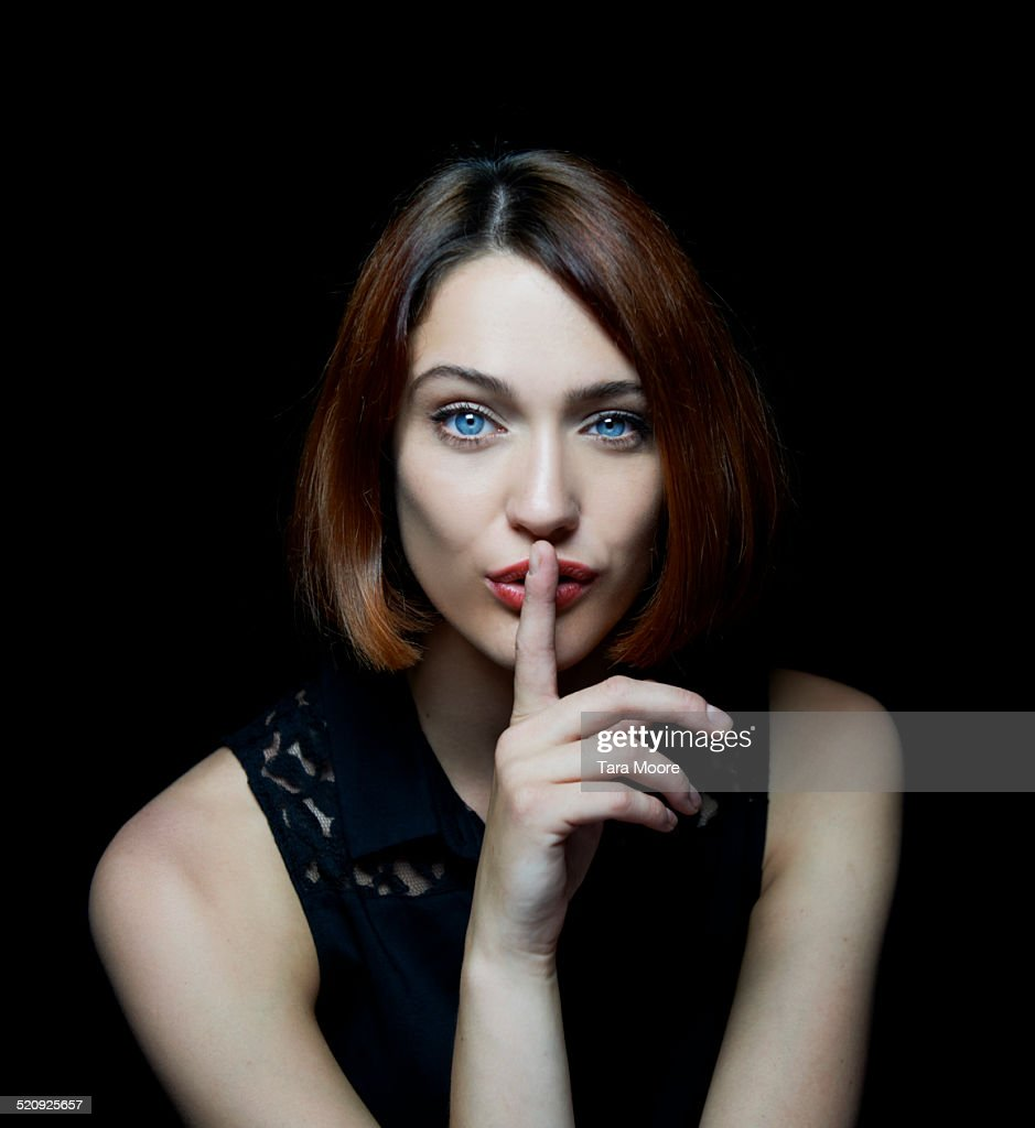 woman shushing with finger up to mouth : Stock-Foto