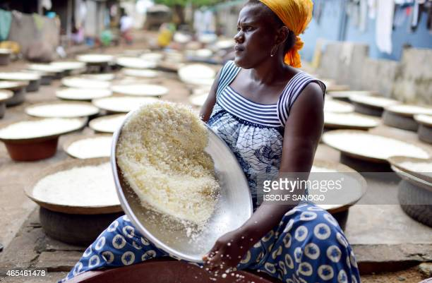 A woman sieves manioc flour in Abidjan on March 6 for the preparation of the Attieke a classic of the Ivorian food Originated from southern Ivory...