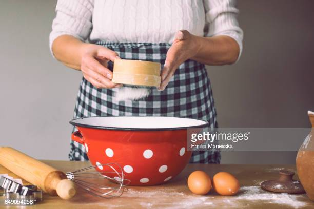 Woman sieving flour in domestic kitchen