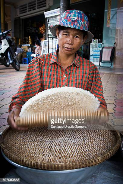 Woman sieving rice at a street in Phnom Penh Cambodia
