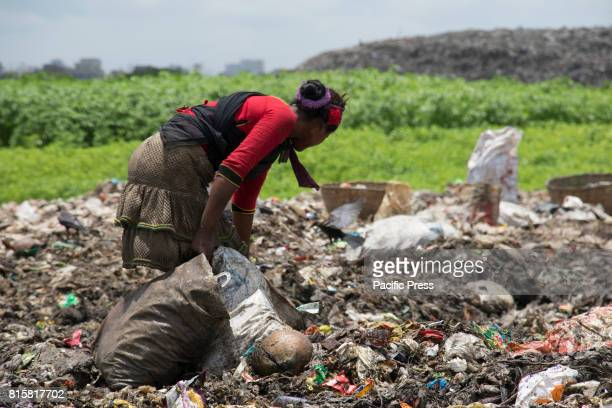 A woman sift through mountains of rubbish searching for anything reusable or recyclable they can sell although it will earn them less than $3 a day...