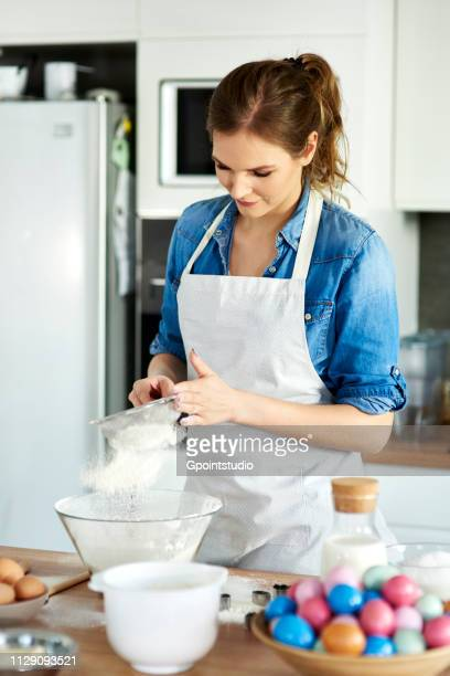 Woman sifting flour into mixing bowl in kitchen