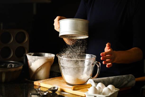 woman sifting flour through sieve. - 焗 預備食物 個照片及圖片檔