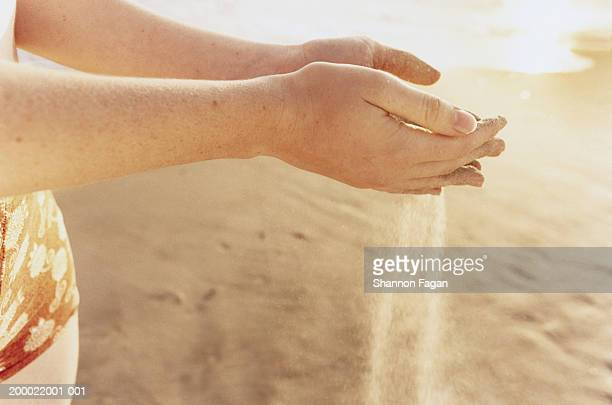 Woman sifting sand through hands at beach, close-up