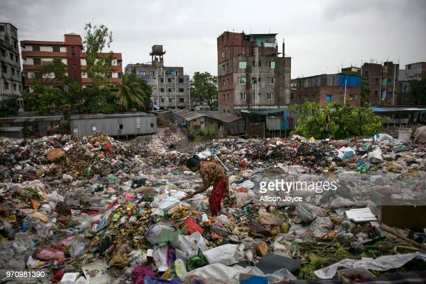A woman sifts through garbage next to a polluted canal that leads to the Buriganga river June 10 2018 in Dhaka Bangladesh Bangladesh has been...