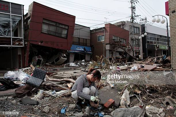 A woman sifts through the rubble of her home on March 17 2011 in Kensennuma Japan Residents were allowed back to their homes today and began the...
