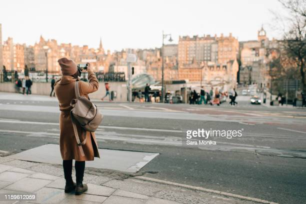 woman sightseeing and taking photo, calton hill, edinburgh, scotland - brown hat stock pictures, royalty-free photos & images