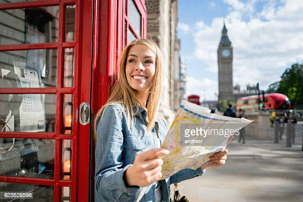 woman sightseeing in london holding a map - toerist stockfoto's en -beelden