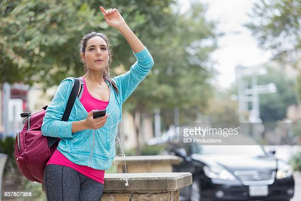 Woman signals to ride while waiting on a city street