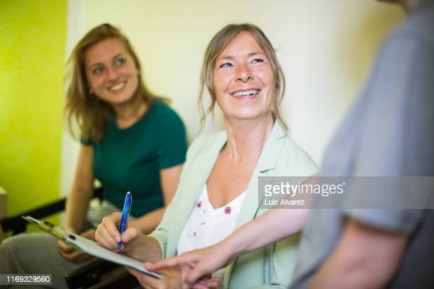 woman signing a form at medical office - questionnaire stock pictures, royalty-free photos & images