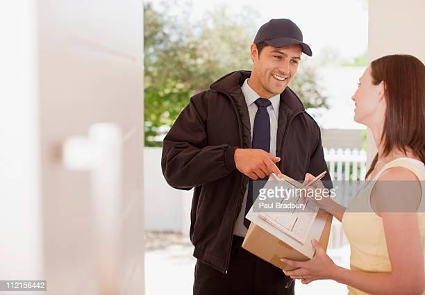 女性の署名ボックスに配達する男性
