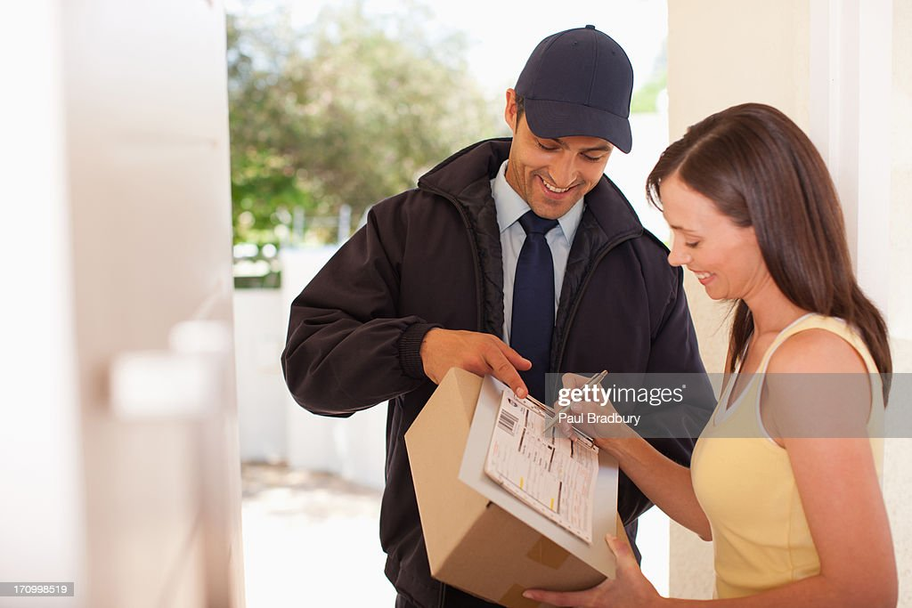 Woman signing box receipt for delivery man : Stockfoto