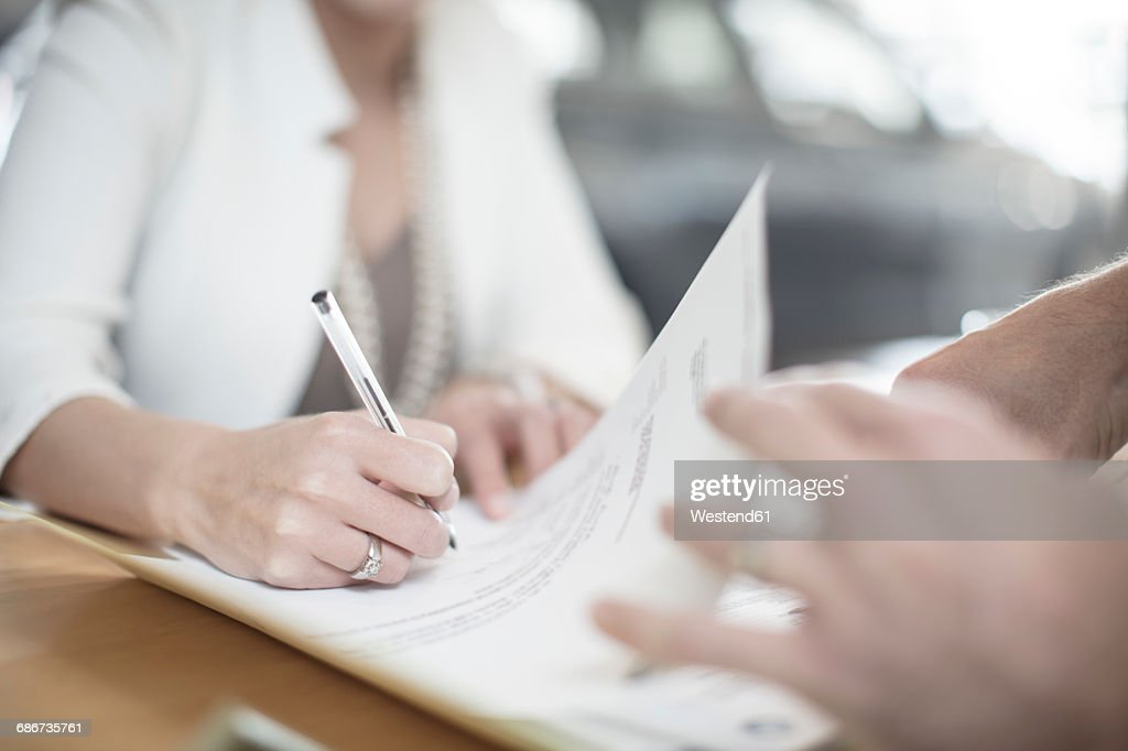 Woman signing contract at desk at car dealership : Stock Photo