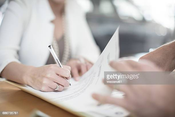 woman signing contract at desk at car dealership - parte del cuerpo humano fotografías e imágenes de stock