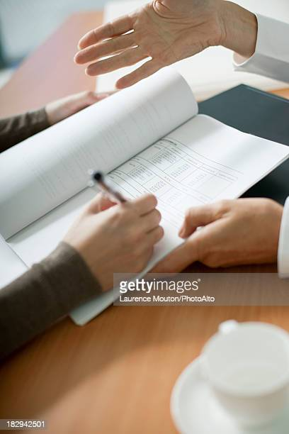 Woman signing contract, cropped
