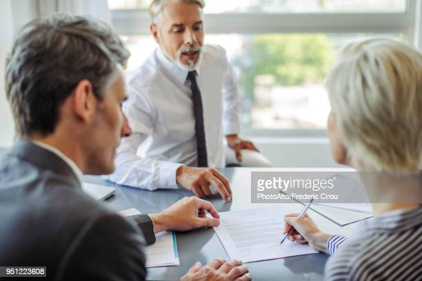 woman signing document in meeting with business professionals - adulte d'âge moyen photos et images de collection