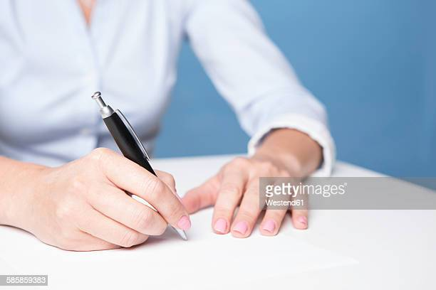 woman signing document on the table - human body part stock pictures, royalty-free photos & images