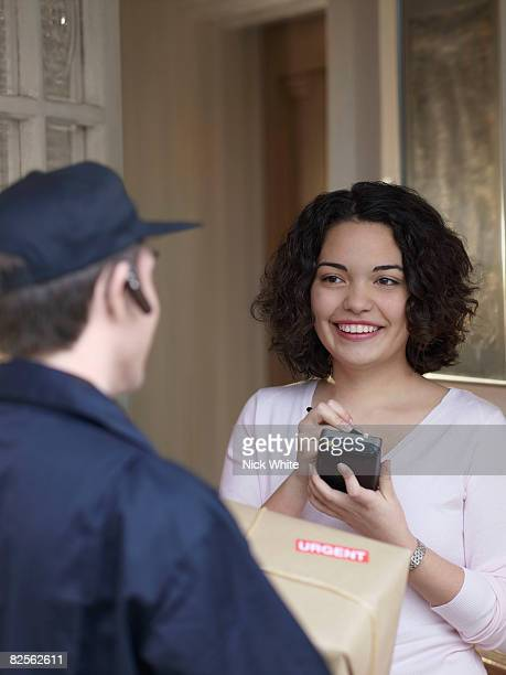 Woman signing for package with courier